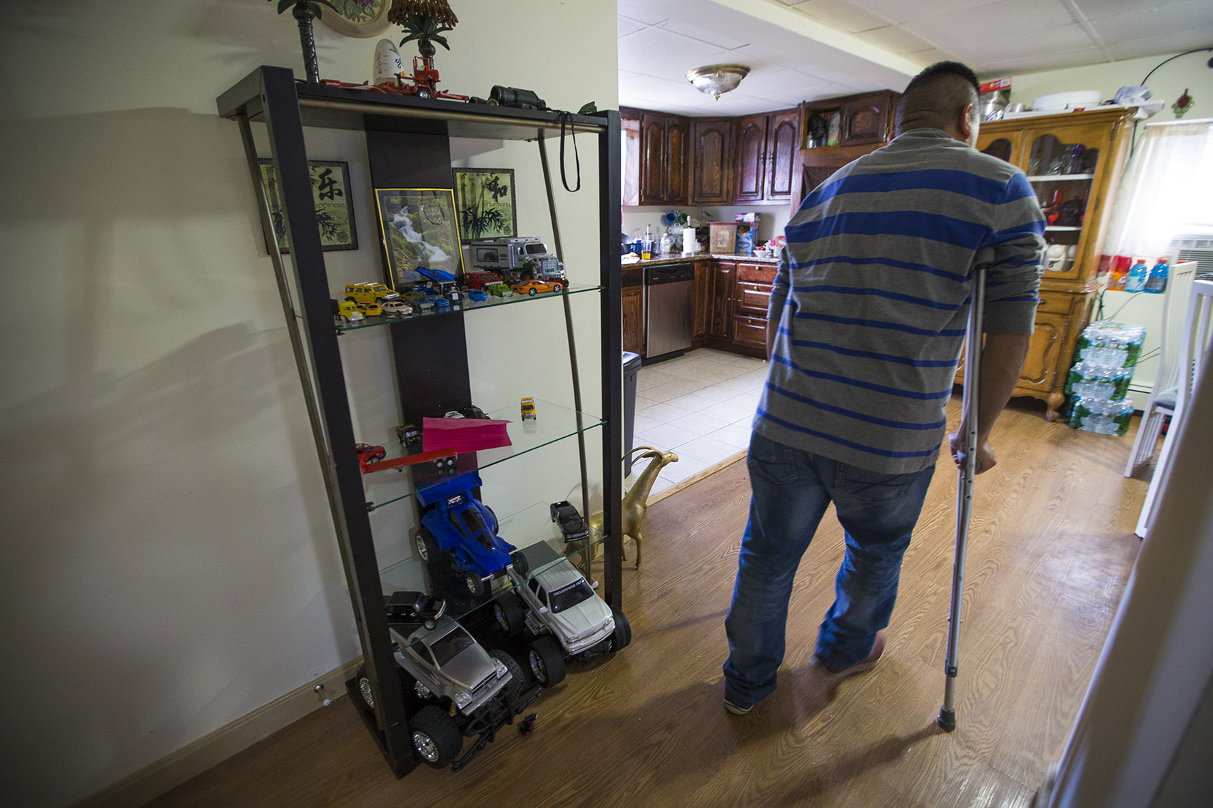 Jose Flores walks through his kitchen on crutches after fracturing his femur bone on a construction site in Boston. (Jesse Costa/WBUR)
