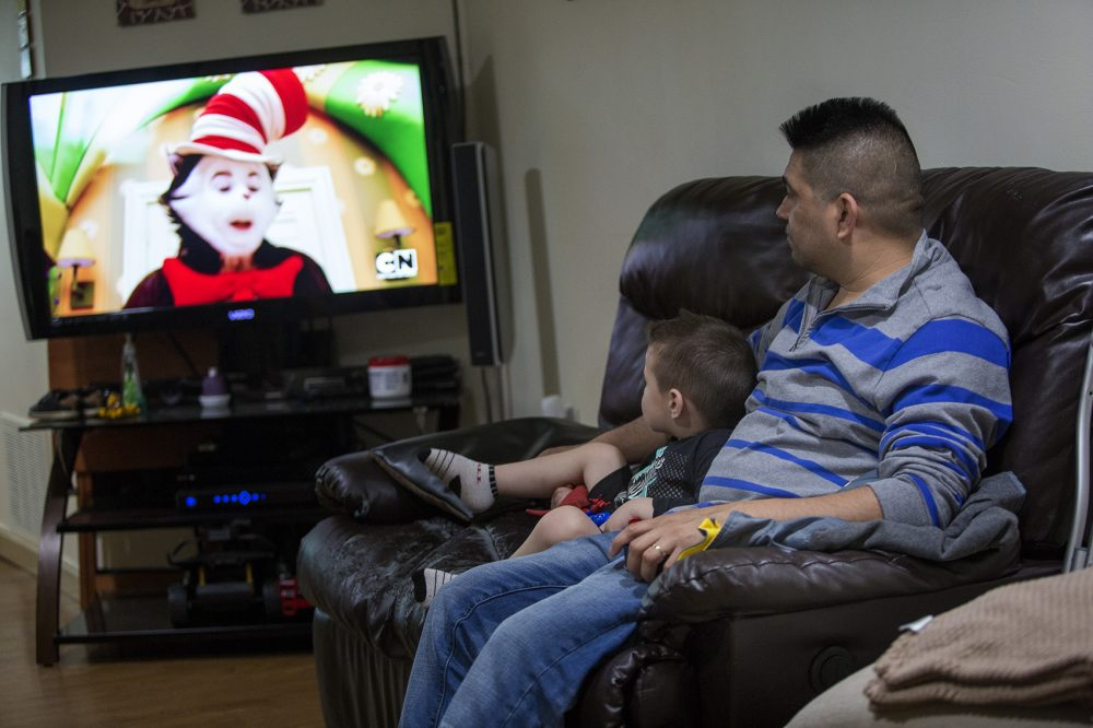 Jose Flores watches television with his young son in 2017. (Jesse Costa/WBUR)