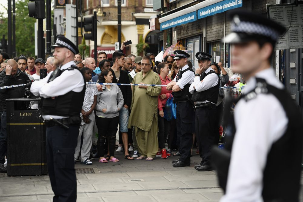 Members of the public view the scene after police officers raided a property in East Ham on June 4, 2017, in London. (Carl Court/Getty Images)