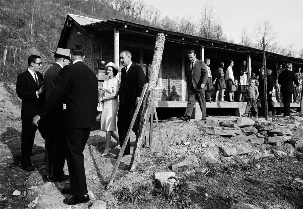President Johnson and his wife are shown leaving the home of Tom Fletcher, father of eight, who told Johnson he'd been out of work for nearly two years.  The president made a trip to eastern Kentucky to see conditions in the region. (AP)