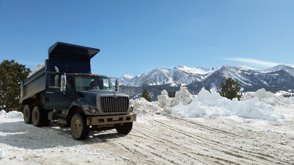 This March 2, 2017 photo provided by the California National Guard shows a Guard dump truck helping to clear huge snow drifts from the Eastern Sierra town of Mammoth Lakes, Calif. (California National Guard via AP)