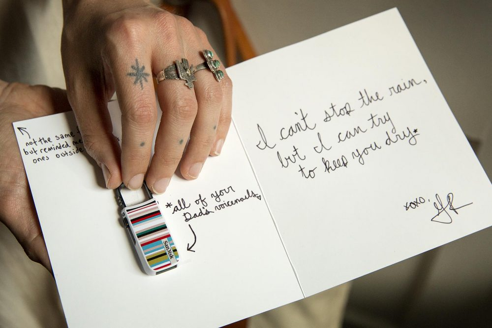 Alice Saunders holds the flash drive of her father's voicemail messages, and the note Greg Ralich wrote when he gave it to her. (Robin Lubbock/WBUR)