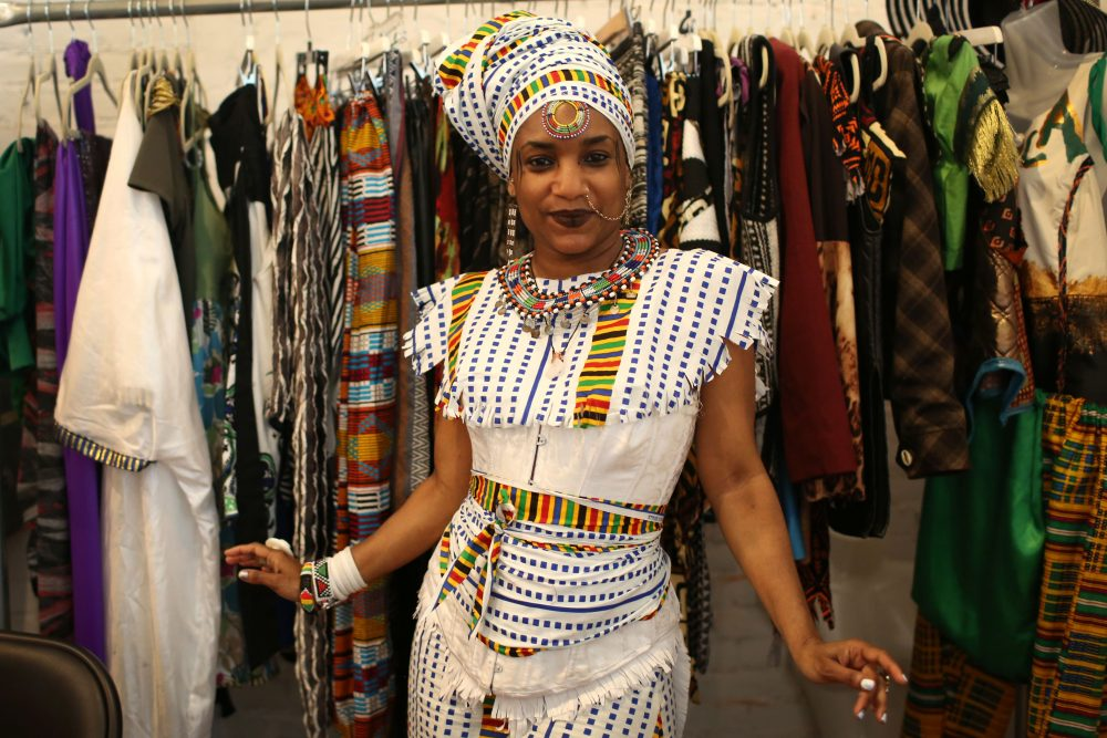 Nahdra Ra Kiros, owner of the clothing company The House of Nahdra, poses in front of her booth at Black Market last year. (Hadley Green for WBUR)