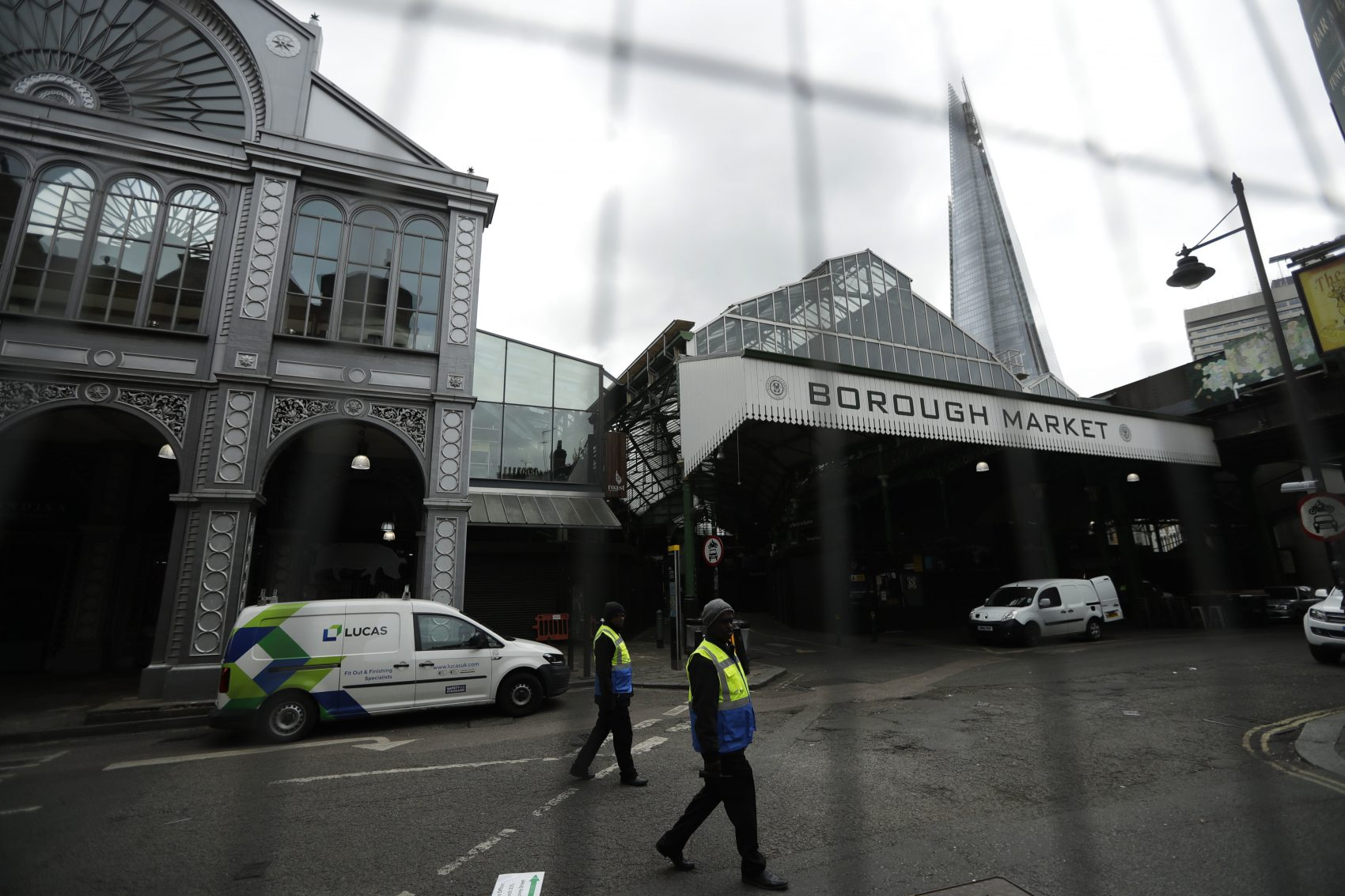Security marshals are seen through a fence walking beside Borough market, in London, which remains closed to the public after the attack that took place there, Monday, June 12, 2017. (Matt Dunham/AP)