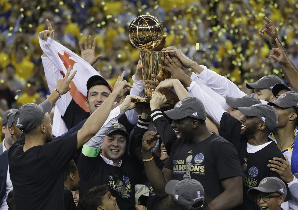 Golden State Warriors players, coaches and owners hold up the Larry O'Brien NBA Championship Trophy after Game 5 of basketball's NBA Finals between the Warriors and the Cleveland Cavaliers in Oakland, Calif., Monday, June 12, 2017. (Marcio Jose Sanchez/AP)