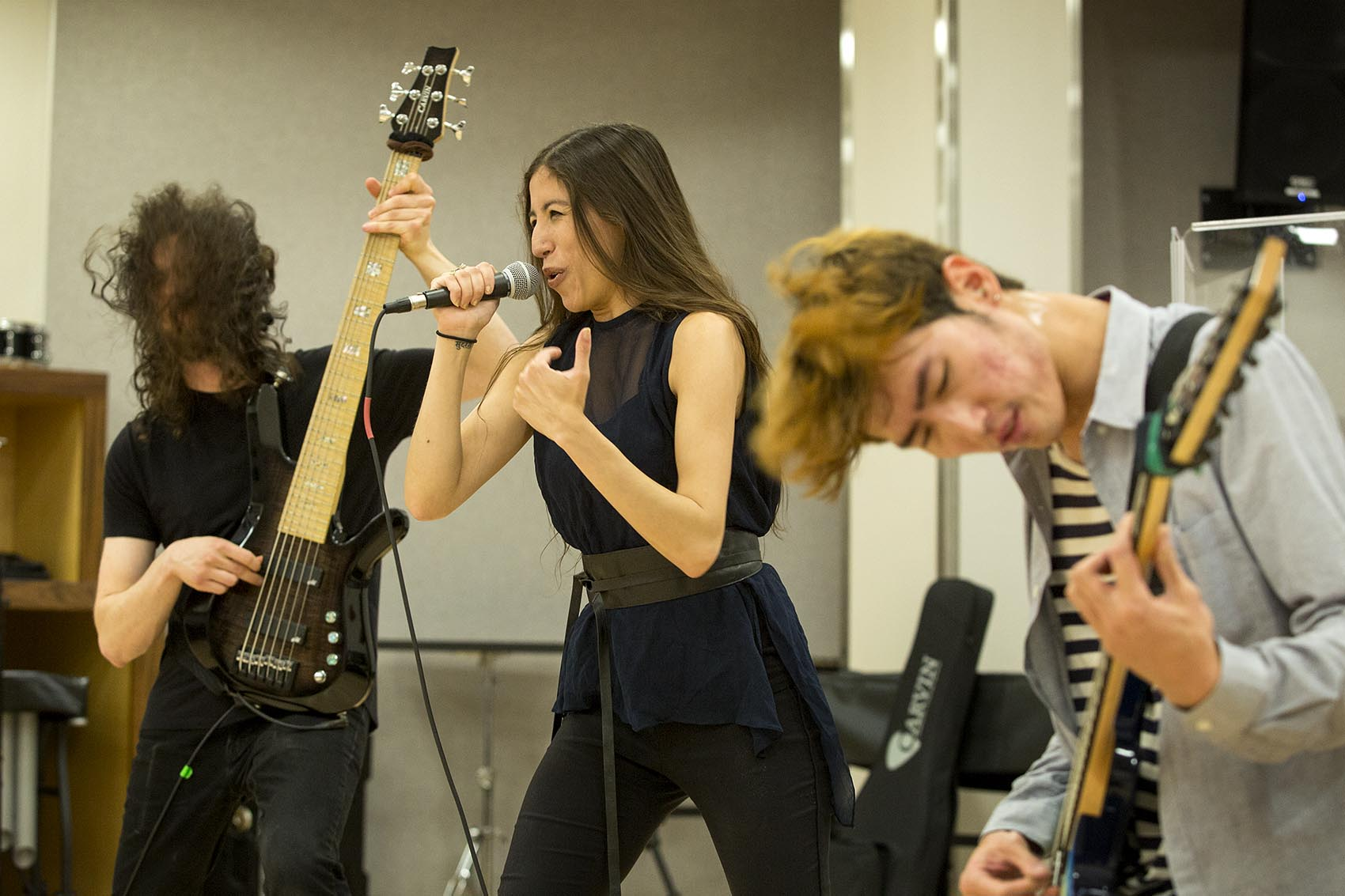 Aversed bassist Martin Epstein, lead singer Haydee Irizarry and lead guitarist Sungwoo Jeong play in a practice room at Berklee College. (Robin Lubbock/WBUR)