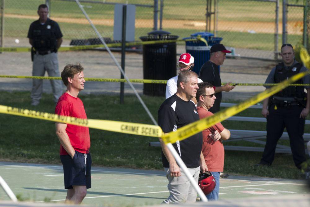 Members of the Republican Congressional softball team stand behind police tape in Alexandria, Va., Wednesday, June 14, 2017, after a multiple shooting involving House Majority Whip Steve Scalise of La. during a congressional baseball practice. (Cliff Owen/AP)