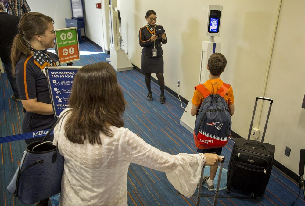 Passengers line up in front of a camera for biometric boarding. (Robin Lubbock/WBUR)