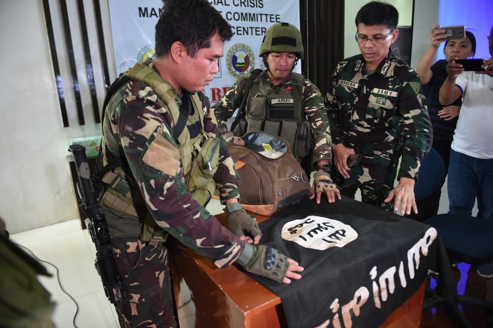 """Philippine Army troopers prepare to display an ISIS flag and 11 kilograms of the illegal drug """"shabu,"""" which were recovered from an Islamist militants position, prior to a press conference at the provincial capitol in Marawi on the southern island of Mindanao on June 19, 2017. (Ted Aljibe/AFP/Getty Images)"""