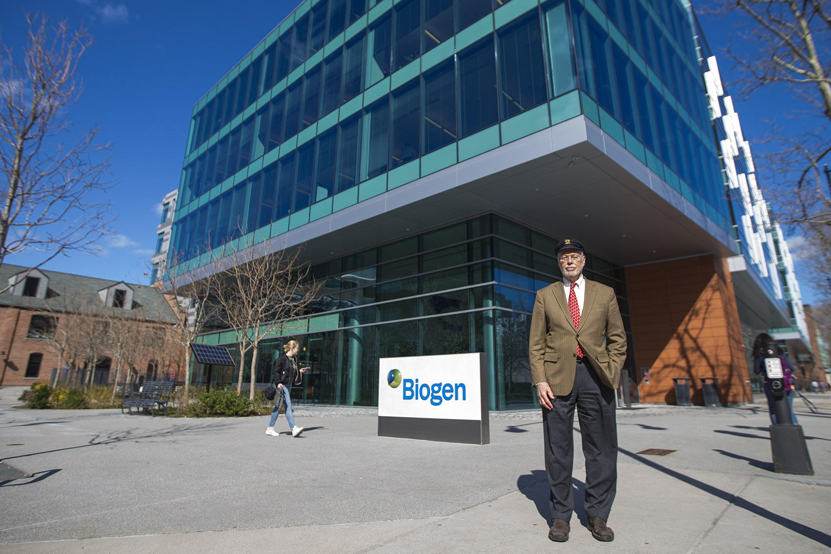 Biogen co-founder Phillip Sharp standing in front of the company's building in Cambridge. (Jesse Costa/WBUR)