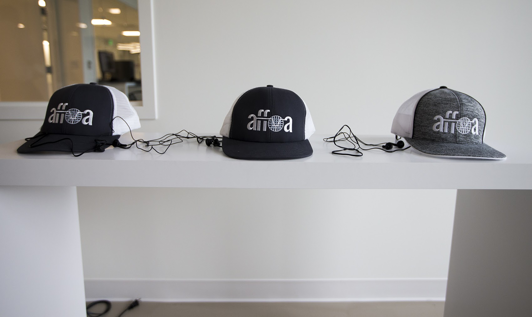 A display table with AFFOA trucker hats. When used with proper LED lighting, the hats can receive optical signals which is then converted to electrical signals to emit sound. (Jesse Costa/WBUR)