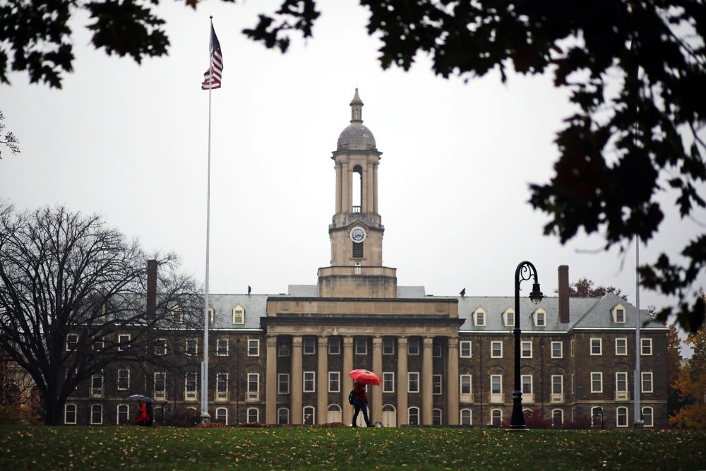 A Penn State student walks past Old Main on the Penn State main campus in State College, Pa., in 2015. (Gene J. Puskar/AP)
