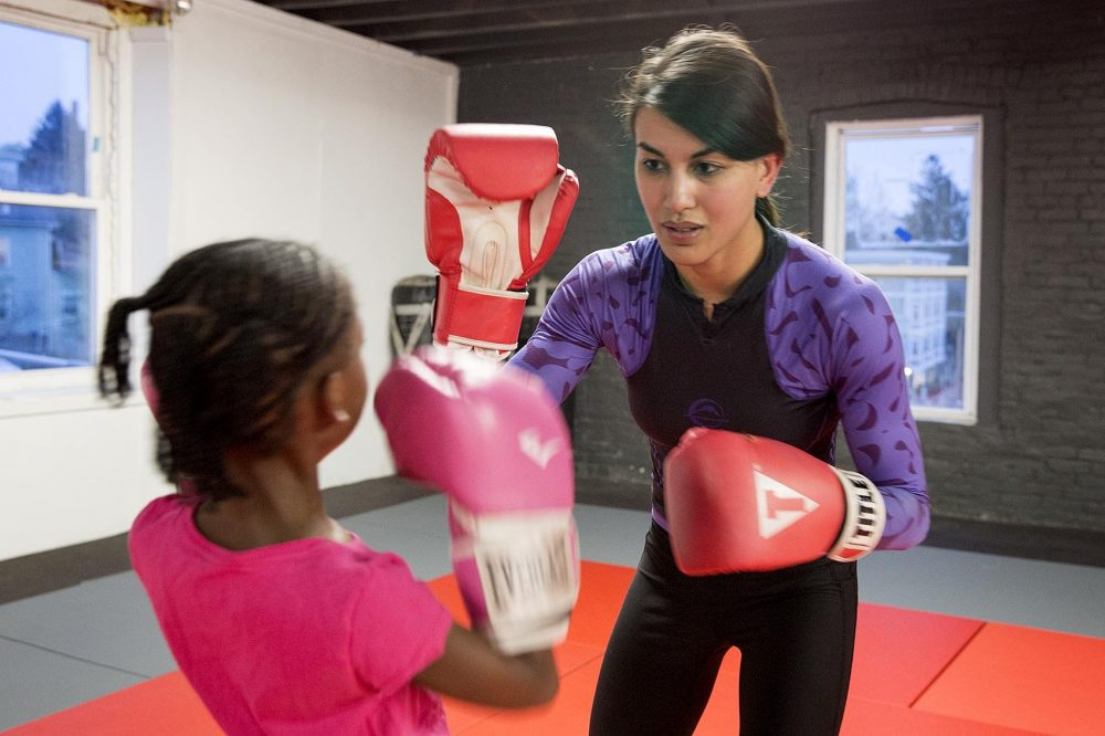 Ali Fuller, founder and CEO of Level Ground MMA, trains with a young student. (Robin Lubbock/WBUR)