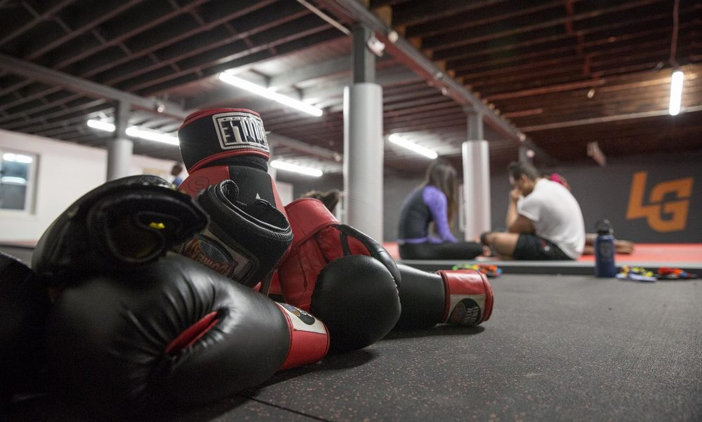 After an evening of sparring, a pile of gloves rests beside the mat at the Level Ground Mixed Martial Arts training center. (Robin Lubbock/WBUR)