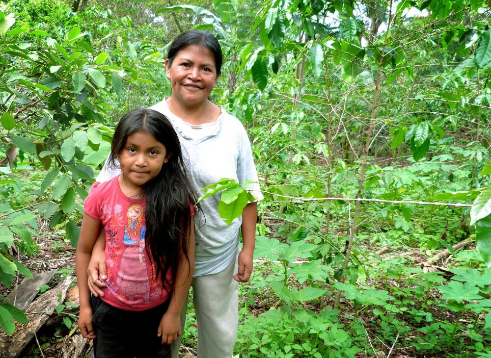 Farmer Dilcia Garcia and daughter Fatima on their farm. Behind her are fruit trees including mangoes and papayas, as well as the more traditional coffee. (Karyn Miller-Medzon/Here & Now)