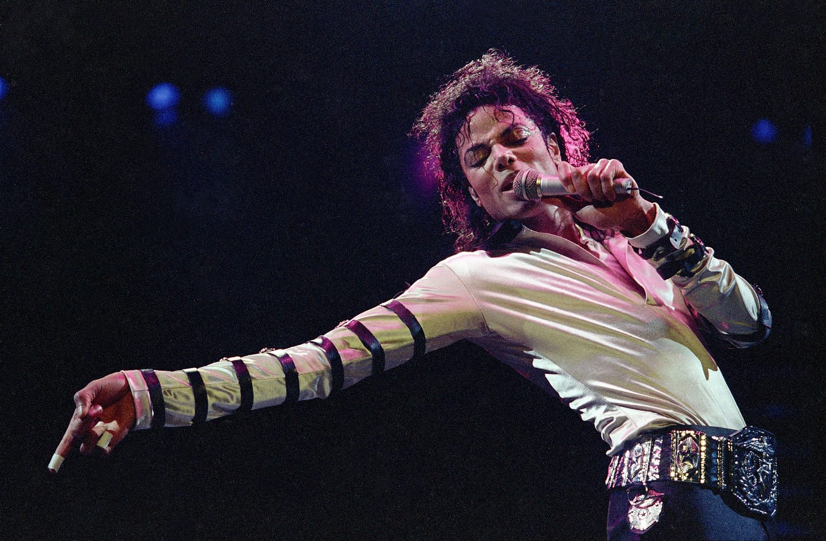 Michael Jackson leans, points and sings during the opening performance of his 13-city U.S. tour, Tuesday, Feb. 24, 1988, in Kansas City. (Cliff Schiappa/AP)