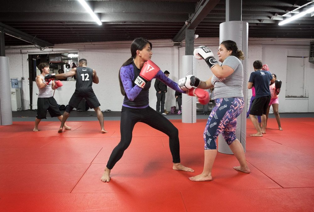 Level Ground founder Alexandra Fuller, left, trains with Alisandra Quiñones, now a three-year veteran of MMA. (Robin Lubbock/WBUR)