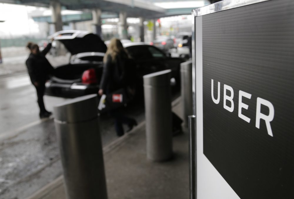 In this March 15, 2017, file photo, a sign marks a pick-up point for the Uber car service at LaGuardia Airport in New York. Travis Kalanick, the combative and embattled CEO of ride-hailing giant Uber, resigned under pressure from investors at a pivotal time for the company. (Seth Wenig/AP)