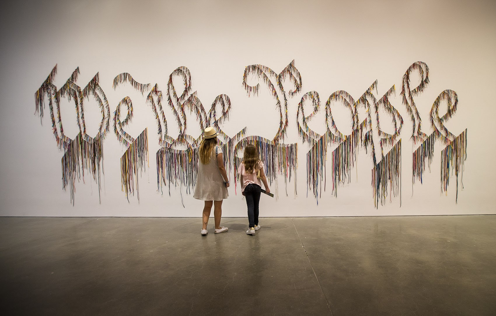 """Visiting the ICA on vacation from Colombia, Maria Alejandra Garcia Velez and her daughter, Maria Jose Cortes Garcia, 9, approach the shoelace work by Nari Ward, """"We the People."""" (Jesse Costa/WBUR)"""