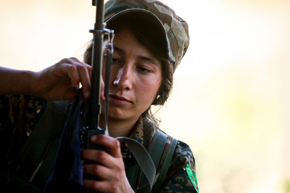 A fighter from the Kurdish female Women's Protection Units adjusts the crosshairs on her rifle during a training exercise in the northeastern Syrian Kurdish town of Derik, on June 1, 2017. (Delil Souleiman/AFP/Getty Images)