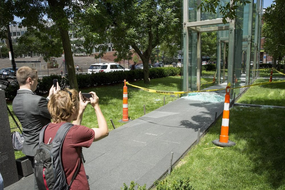 People take photos of the damage to the New England Holocaust Memorial in Boston Wednesday morning. A 21-year-old Boston man is facing charges he vandalized the memorial. (Robin Lubbock/WBUR)