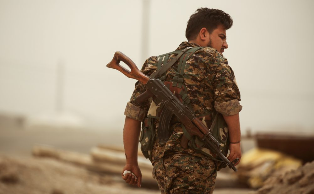 A member of the Kurdish People's Protection Units (YPG) walks with a Kalashnikov assault rifle in the town of al-Karamah, 26 kilometers from the Islamic State group bastion of Raqqa, on May 10, 2017. (Delil Souleiman/AFP/Getty Images)