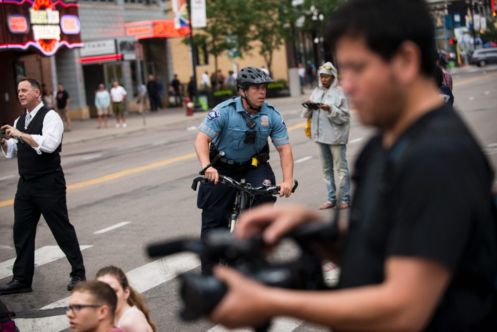 A police officer bikes through a protest on July 17, 2017 in Minneapolis, Minn. Demonstrations have taken place each day since a jury acquitted police officer Jeronimo Yanez in the shooting death of Philando Castile. (Stephen Maturen/AFP/Getty Images)