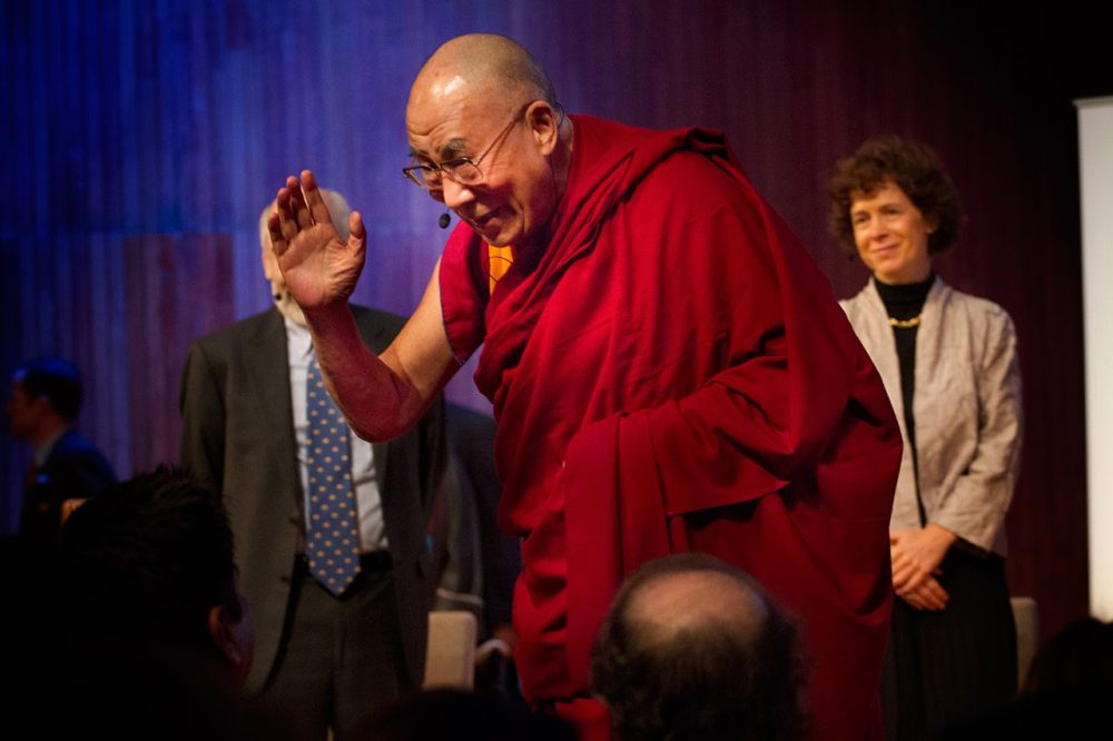 """Tibetan exiled spiritual leader the Dalai Lama waves as he takes the stage for the """"Ethics, Economy and Environment Panel"""" at the Global Systems 2.0 Conference at MIT on October 15, 2012. (Jesse Costa/WBUR)"""