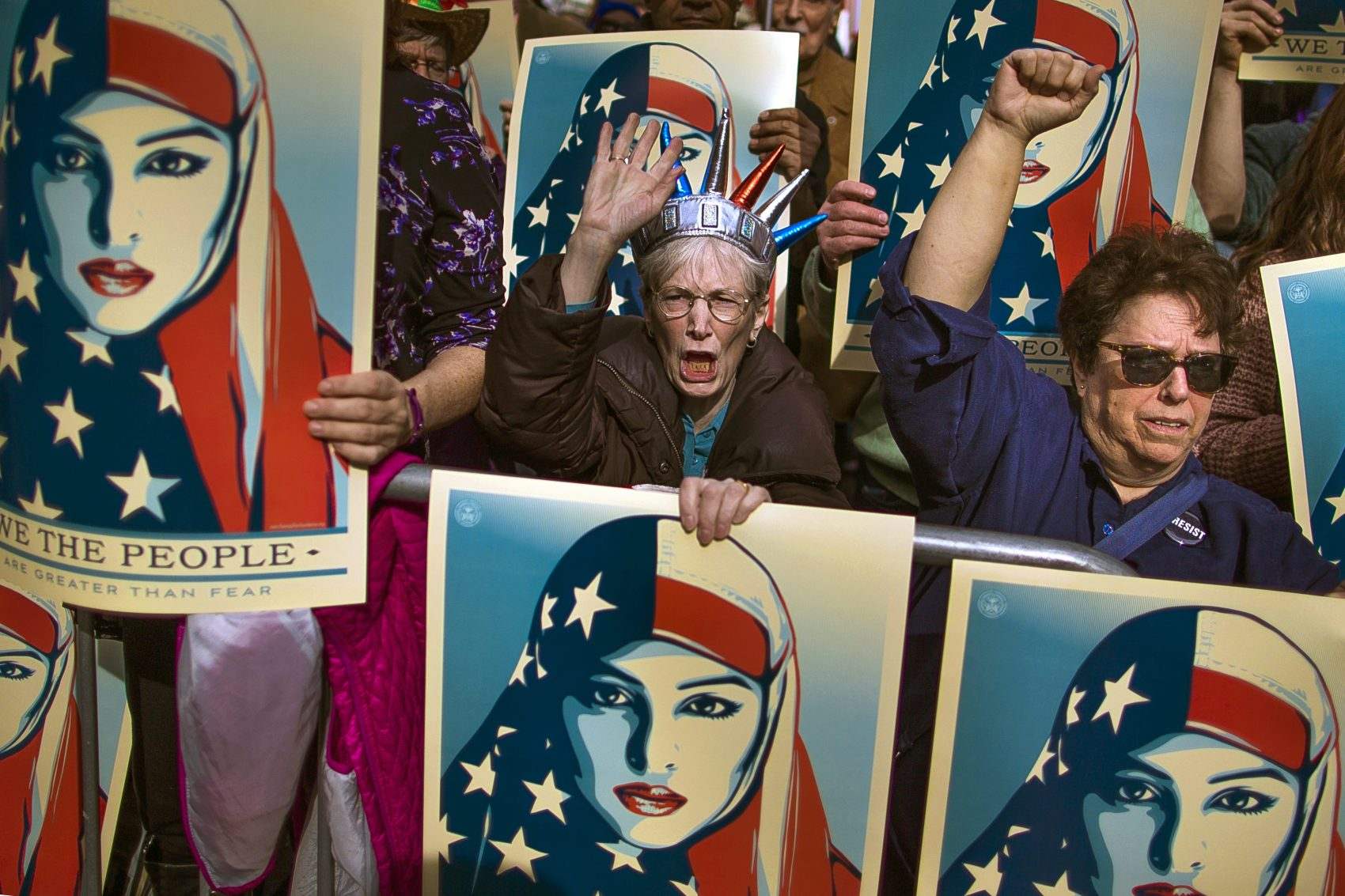 On Feb. 19, 2017, people carry posters during a rally against President Donald Trump's first executive order banning travel from seven Muslim-majority nations, in New York's Times Square. (Andres Kudacki/AP)