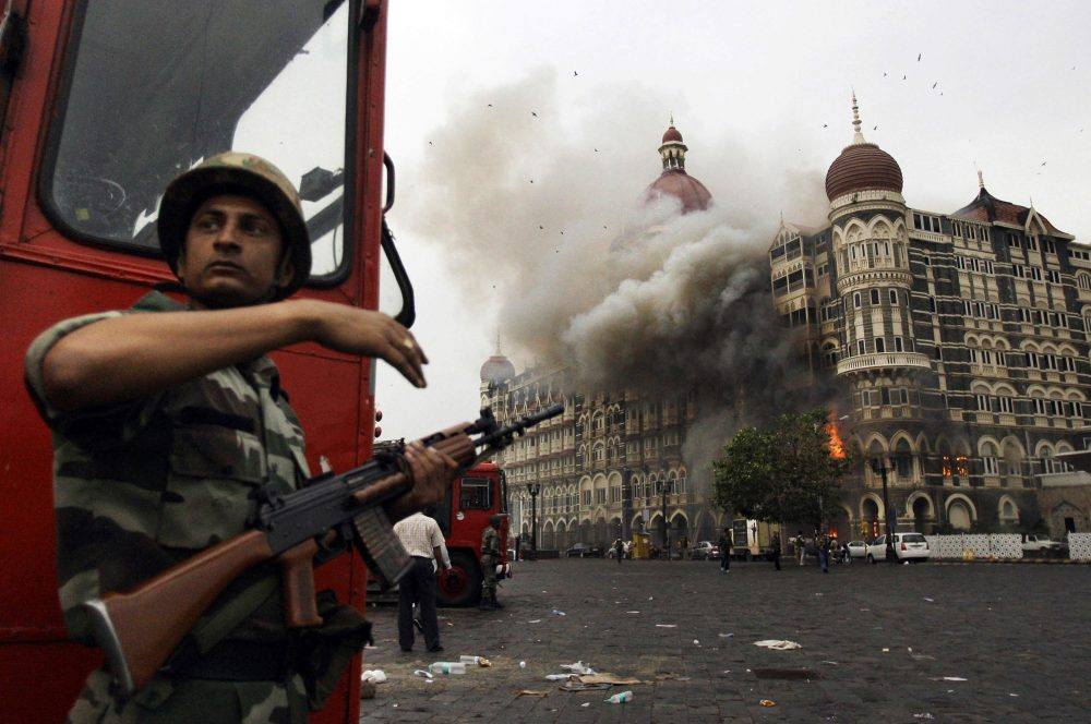 In this 2008 file photo, an Indian soldier takes cover as the Taj Mahal hotel in Mumbai burns during a gun battle between Indian military and militants. Pakistani-American David Headley helped the 2008 attack. (David Guttenfelder/AP)