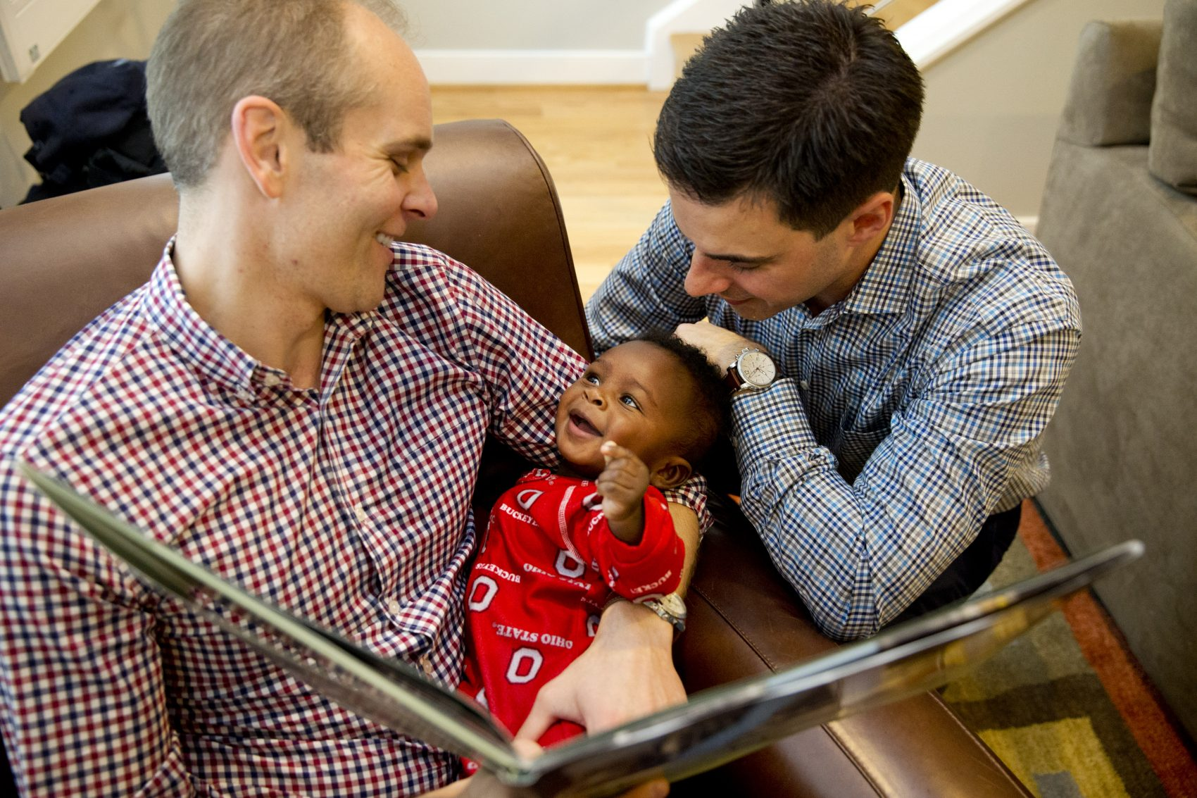 Gregg Pitts, left, and Brooks Brunson read to their son, Thomas Brunson-Pitts, 6 months, before heading to work in the morning at their home in Washington, on May 19, 2016.  (Jacquelyn Martin/AP)