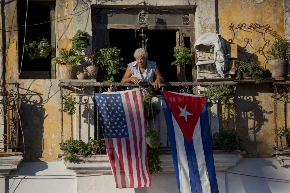 Javier Yanez stands on his balcony decorated with U.S. and Cuban flags in Old Havana, Cuba on Dec. 19, 2014. (Ramon Espinosa/AP)