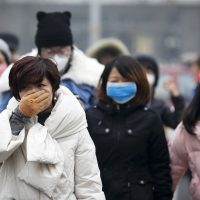 A woman uses her hand to cover her face from pollutants as people walk along a street on a polluted day in Beijing, Tuesday, Dec. 8, 2015. (Andy Wong/AP)