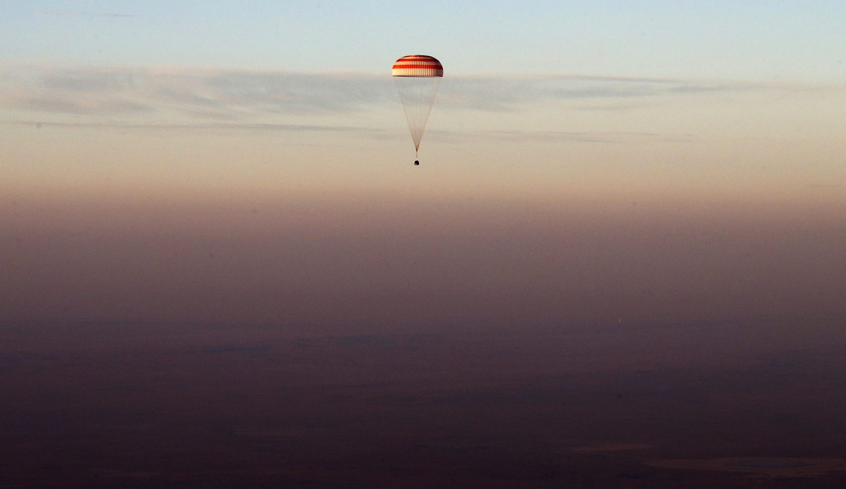Just go with me here, writes Joelle Renstrom. Suspend your disbelief.  Pictured: The Soyuz TMA-19M capsule carrying NASA's Jeff Williams, and two Russian cosmonauts descends beneath a parachute over Kazakhstan, in Sept., 2016 after a six-month mission aboard the International Space Station. (Maxim Shipenkov/AP)