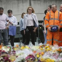 The fear of another attack is something that has become embedded in our collective consciousness, writes Justin Sinclair, whether we realize it or not. Pictured: City workers and others stand after laying flower tributes in London for victims of the terrorist attack on London Bridge, on Monday, June 5, 2017. (Tim Ireland/AP)
