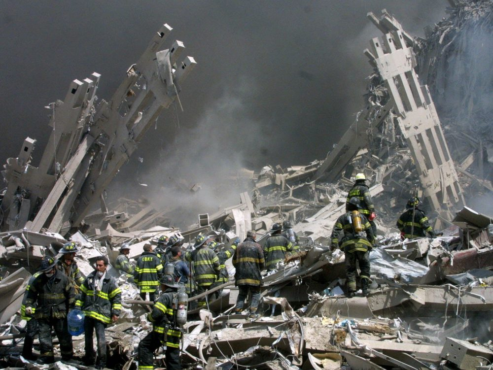 Firefighters make their way through the rubble after two airliners crashed into the World Trade Center in New York on Sept. 11, 2001. (Shawn Baldwin/AP)