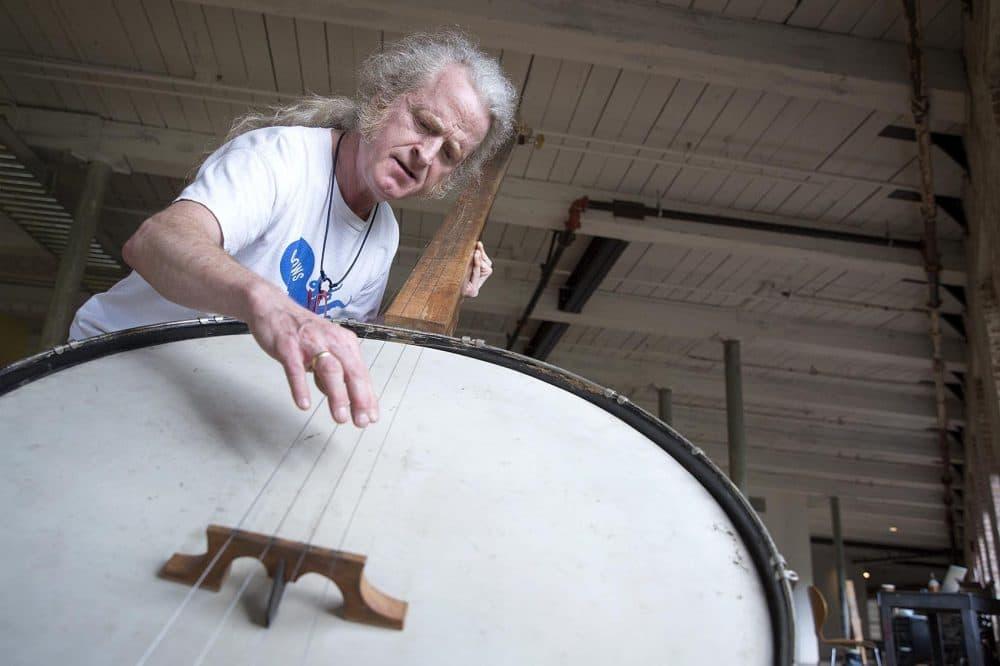 Musician Mark Stewart plays a giant banjo created by Gunnar Schonbeck. (Robin Lubbock/WBUR)