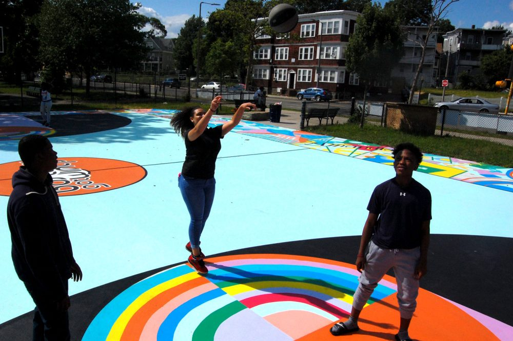 "Playing on Maria Molteni's ""Hard In the Paint"" basketball court mural at Boston's Harambee Park. (Greg Cook/WBUR)"