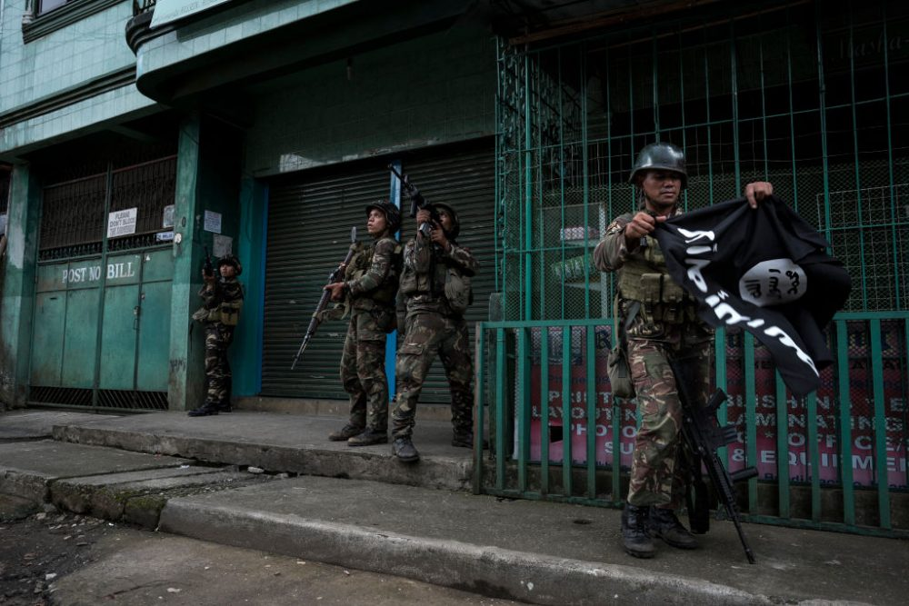 A soldier carrying a captured ISIS flag while clearing a city street of militants on May 26, 2017 in Marawi city, southern Philippines. (Jes Aznar/Getty Images)