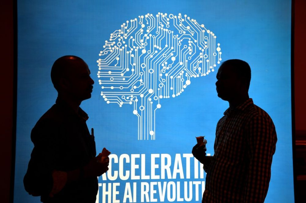 Participants at Intel's Artificial Intelligence (AI) Day stand in front of a poster during the event in the Indian city of Bangalore on April 4, 2017. (Manjunath Kiran/AFP/Getty Images)