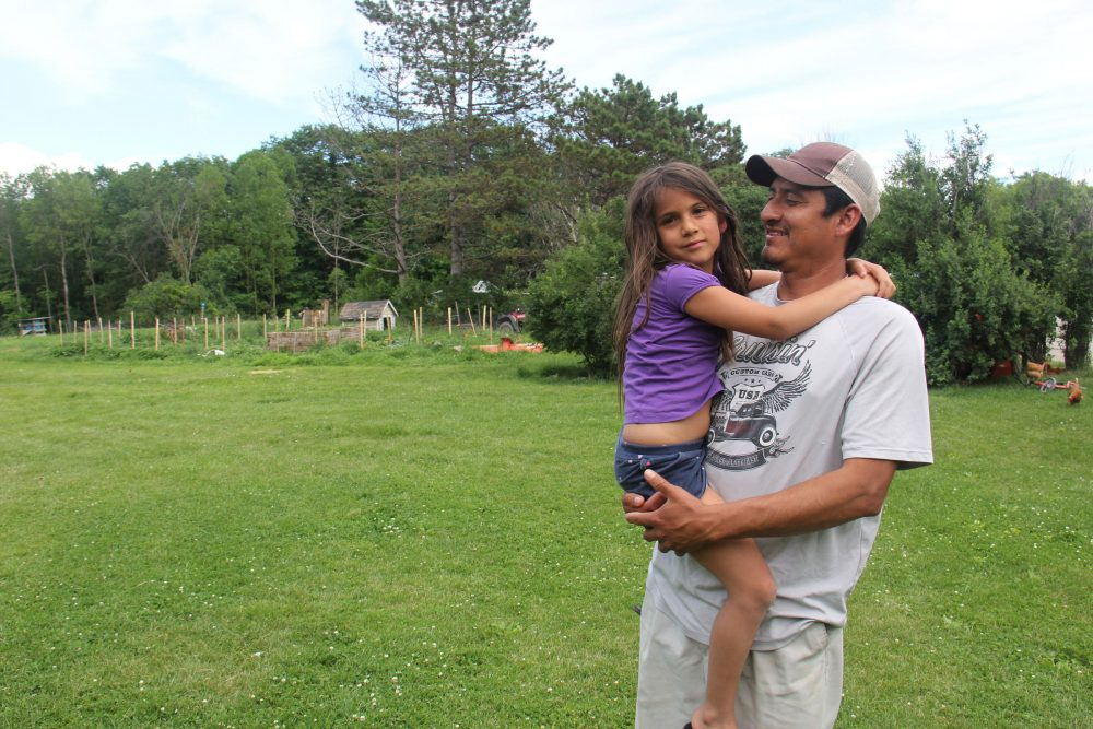Juan De La Cruz comforts his youngest daughter, Isabella, at their home in Vergennes. (Kathleen Masterson/VPR)