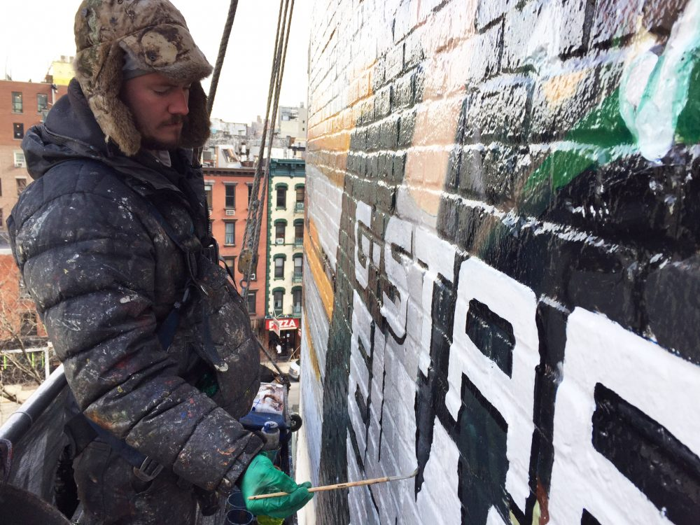 Liam McWilliams works on a hand-painted billboard in lower Manhattan. (Topher Forhecz)