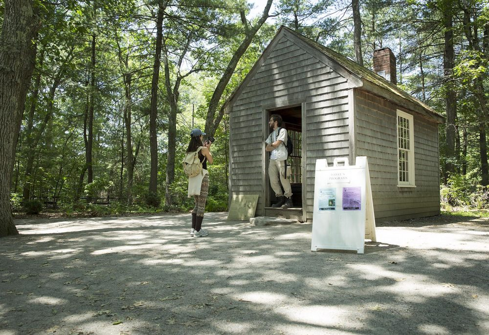 Visitors take photos at the replica of Henry David Thoreau's Walden Pond cabin. Notes Thoreau took during his time at the pond are helping scientists study climate change. (Robin Lubbock/WBUR)