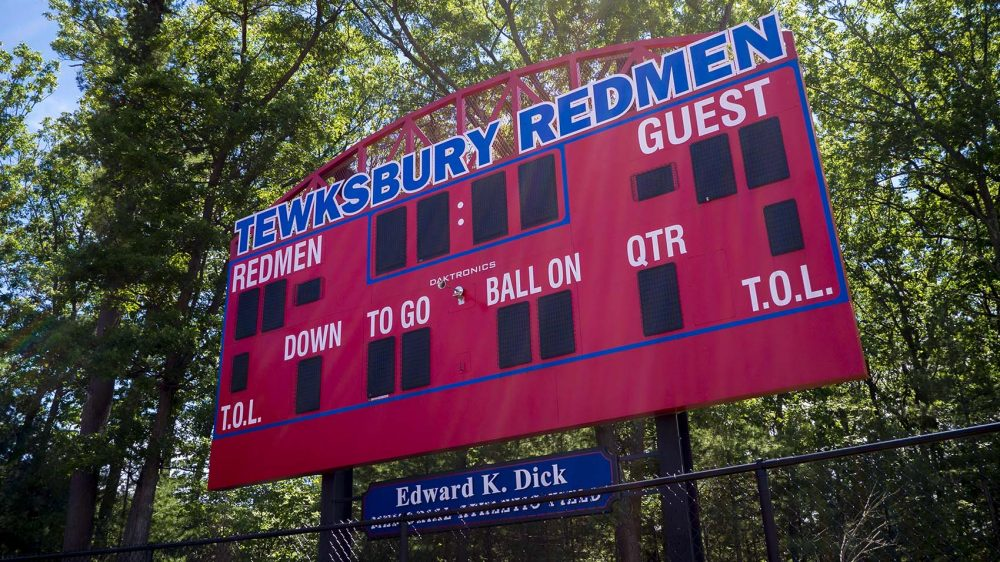 A group of citizens have proposed banning native-themed mascots at Massachusetts schools, but the state's native residents are divided -- sometimes pitting the young against their elders. Here, the scoreboard is seen at Tewksbury Memorial High School's athletic fields, the home of the so-called Redmen. (Max Larkin/WBUR)