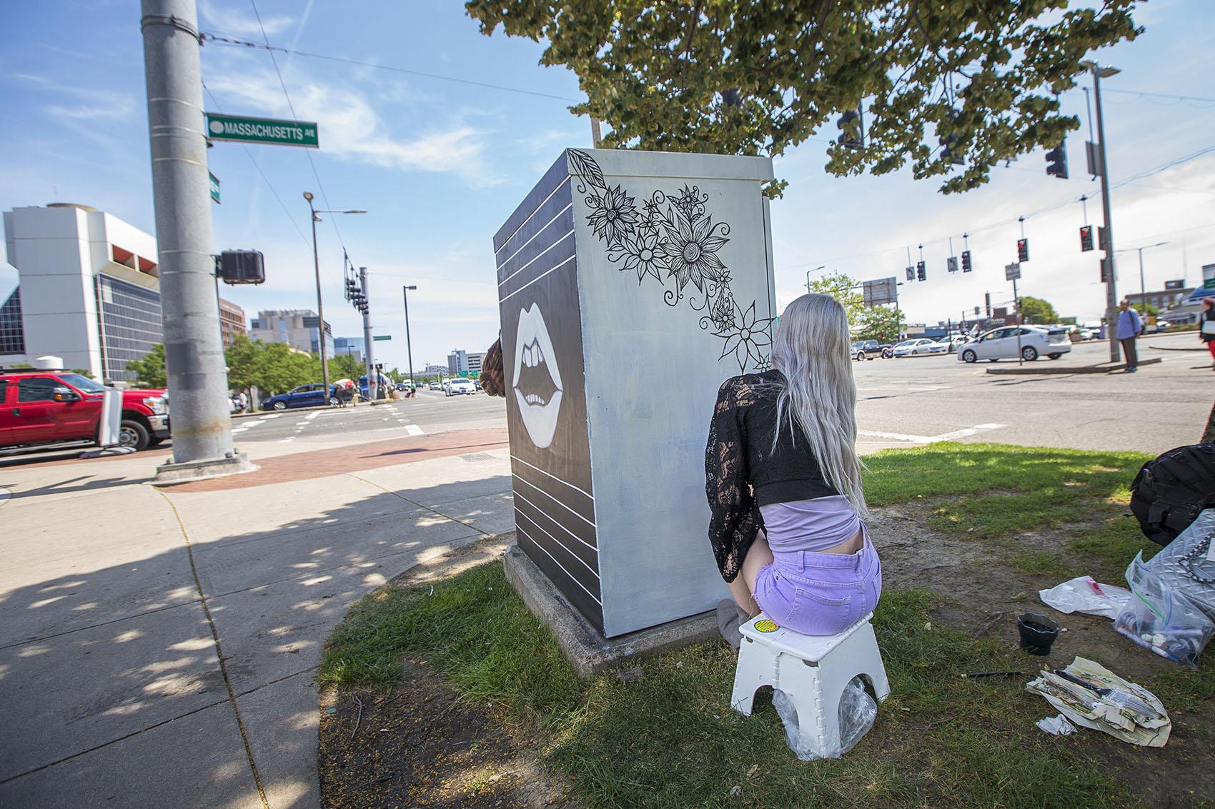 Artist Kitty Zen draws a design on an electrical box at the corner of Massachusetts Avenue and Melnea Cass Boulevard. (Jesse Costa/WBUR)