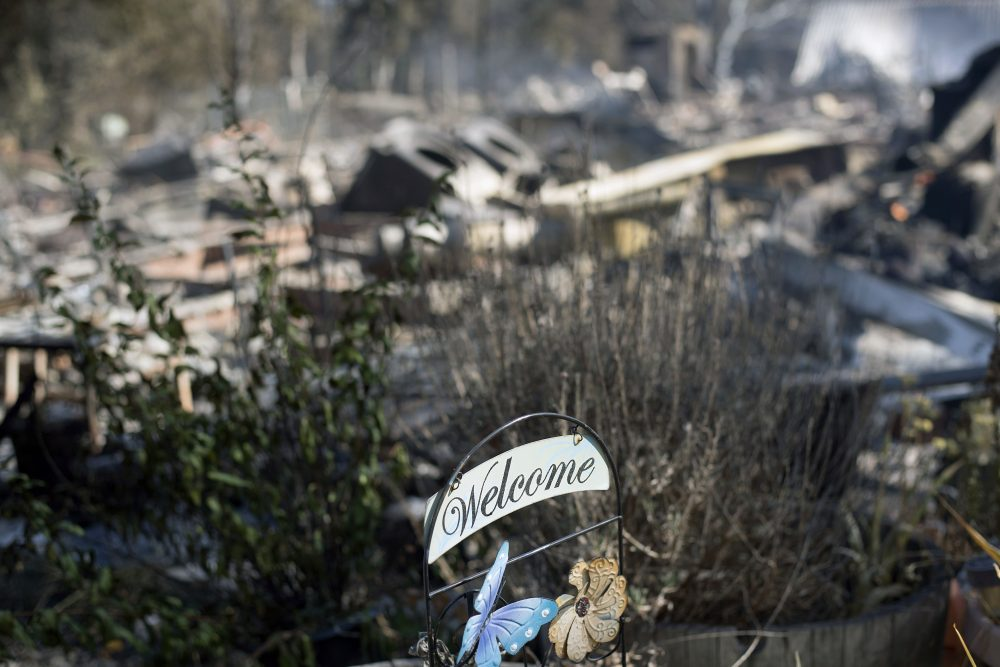 A welcome sign rests in front of residence leveled by a wildfire Sunday, July 9, 2017, near Oroville, Calif. Wildfires barreled across the baking landscape of the western U.S. and Canada, destroying a smattering of homes and forcing thousands to flee. (Noah Berger/AP)