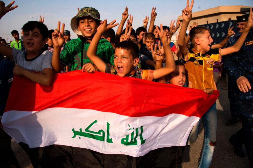 "Children holding Iraq's national flag react as Iraqi forces celebrate in the Old City of Mosul on July 9, 2017 after the government's announcement of the ""liberation"" of the embattled city.  Iraq declared victory against the Islamic State group in Mosul on July 9 after a grueling months-long campaign, dealing the biggest defeat yet to the jihadist group. (Fadel Senna/AFP/Getty Images)"