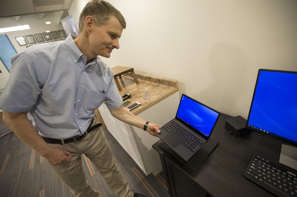 Morris Kesler, WiTricity's chief technology officer, places Dell's new wireless charging laptop on a charging pad. The computer charges through magnetic resonance technology developed at Watertown-based WiTricity. (Jesse Costa/WBUR)