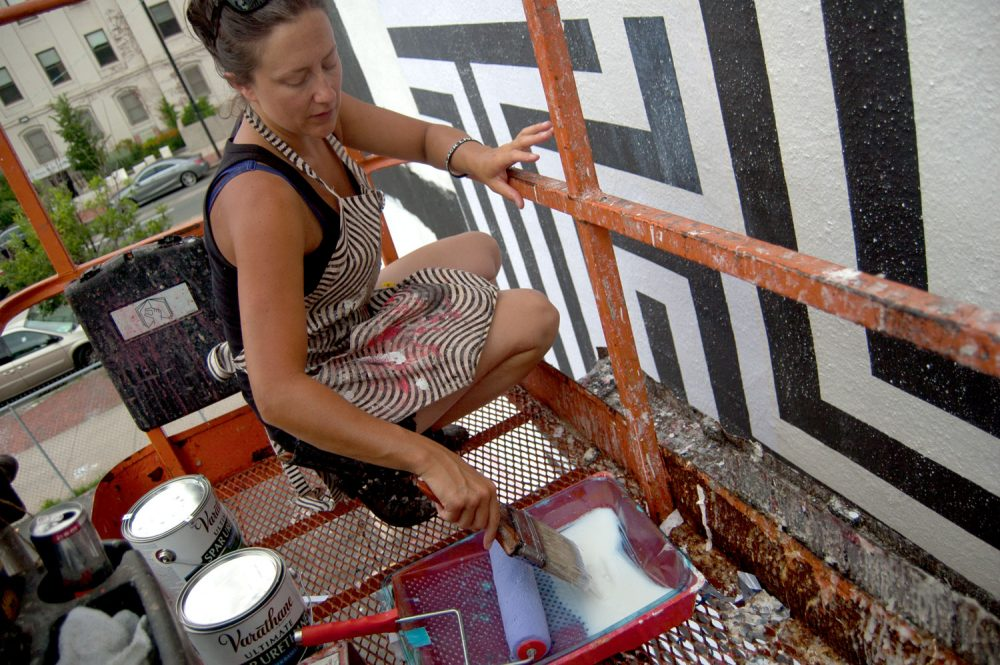 "Ann Lewis works on her mural ""See Her."" (Greg Cook/WBUR)"