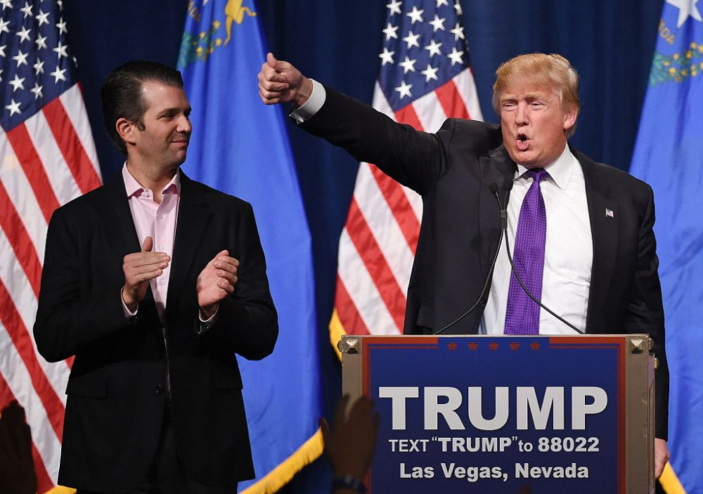 Donald Trump Jr. (left) looks on as his father, then-Republican presidential candidate Donald Trump, waves after speaking at a caucus night watch party at the Treasure Island Hotel & Casino on February 23, 2016 in Las Vegas, Nev. (Ethan Miller/Getty Images)